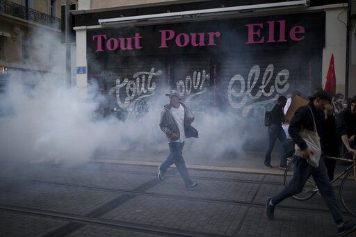 A protester reacts to tear gas fired by French riot police during a march against police brutality and racism in Marseille, France, Saturday, June 13, 2020, organized by supporters of Adama Traore, who died in police custody in 2016. Several demonstrations went ahead Saturday inspired by the Black Lives Matter movement in the U.S.