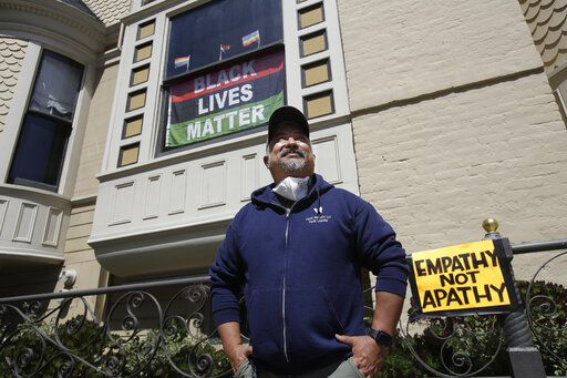 "James Juanillo poses outside of his home in San Francisco, Sunday, June 14, 2020. The CEO of a cosmetic company issued an apology Sunday after she and her husband confronted Juanillo and threatened to call police because he stenciled ""Black Lives Matter"" in chalk on his San Francisco property, as the couple asserted that they know Juanillo doesn't live there and is therefore breaking the law."