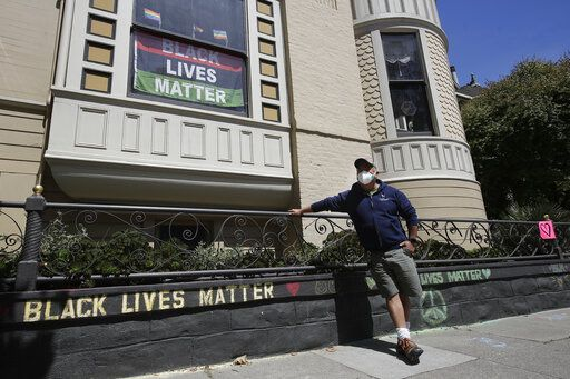 "James Juanillo poses with chalk written outside of his home in San Francisco, Sunday, June 14, 2020. The CEO of a cosmetic company issued an apology Sunday after she and her husband confronted Juanillo and threatened to call police because he stenciled ""Black Lives Matter"" in chalk on his San Francisco property, as the couple asserted that they know Juanillo doesn't live there and is therefore breaking the law."