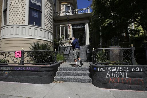 "James Juanillo waves to people as he walks to his home in San Francisco, Sunday, June 14, 2020. The CEO of a cosmetic company issued an apology Sunday after she and her husband confronted Juanillo and threatened to call police because he stenciled ""Black Lives Matter"" in chalk on his San Francisco property, as the couple asserted that they know Juanillo doesn't live there and is therefore breaking the law."