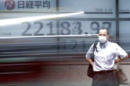 A man stands in front of an electronic stock board showing Japan's Nikkei 225 index as a car passes by at a securities firm in Tokyo Monday, June 15, 2020. Asian shares were mostly lower Monday on concern over a resurgence of coronavirus cases and pessimism after Wall Street posted its worst week in nearly three months.
