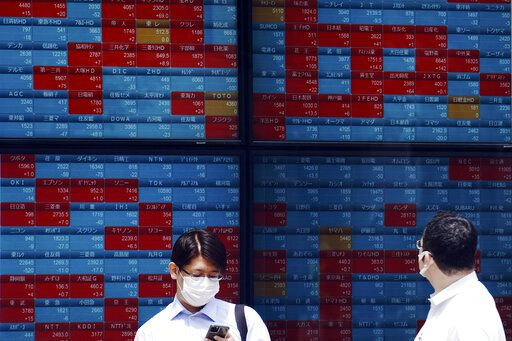 Men stand in front of an electronic stock board showing Japan's Nikkei 225 index at a securities firm in Tokyo Monday, June 15, 2020. Asian shares were mostly lower Monday on concern over a resurgence of coronavirus cases and pessimism after Wall Street posted its worst week in nearly three months.