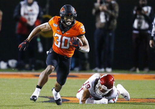 FILE - In this Nov. 30, 2019, file photo, Oklahoma State running back Chuba Hubbard (30) carries past Oklahoma linebacker Caleb Kelly during an NCAA college football game in Stillwater, Okla. Hubbard said on Twitter that he won't do anything with the program until there is change after coach Mike Gundy was photographed wearing a T-shirt representing far-right online publication One America News Network. Gundy is seen in a photograph on Twitter wearing the T-shirt with the letters OAN.