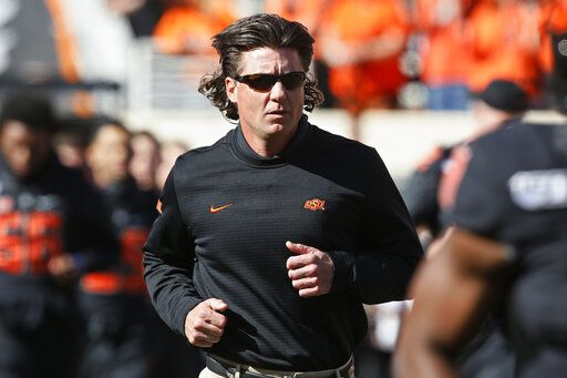 FILE - In this Nov. 2, 2019, file photo, Oklahoma State coach Mike Gundy runs onto the field before the team's NCAA college football game against TCU in Stillwater, Okla. Hubbard said on Twitter that he won't do anything with the program until there is change after Gundy was photographed wearing a T-shirt representing far-right online publication One America News Network. Gundy is seen in a photograph on Twitter wearing the T-shirt with the letters OAN.