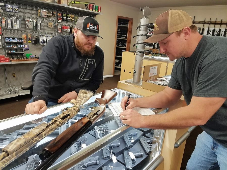 Cody Jones, left, owner of Jones & Son Guns in Du Quoin, watches customer Robbie Tilley Jr. fill out paperwork for a potential purchase in 2019.