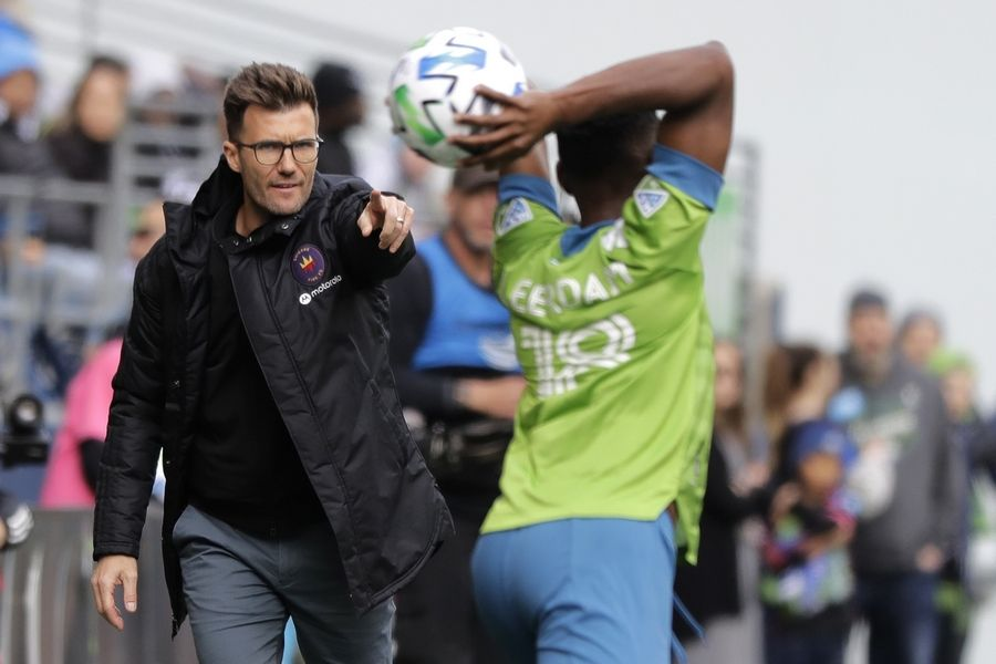 Chicago Fire head coach Raphael Wicky, left, gestures as Seattle Sounders defender Kelvin Leerdam throws the ball in during the first half of an MLS soccer match, Sunday, March 1, 2020, in Seattle.