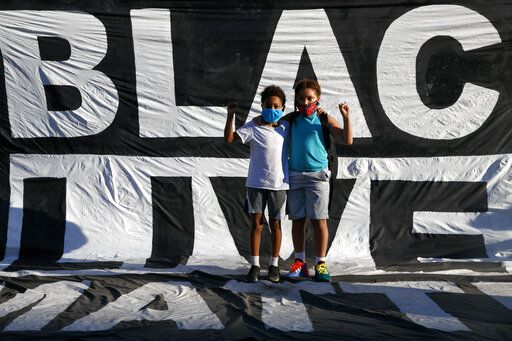 FILE - In this June 7, 2020, file photo, Khai Rieara, 10, left, and his brother Keanu Rieara, 12, of Frederick, Md., stand on the Black Lives Matter banner that is draped on the fence surrounding Lafayette Park, for a photograph as they attend a protest near the White House in Washington. Black Lives Matter Global Network Foundation, the group behind the emergence of the Black Lives Matter movement, has established a more than $12 million fund to aid organizations fighting institutional racism in the wake of the George Floyd protests.
