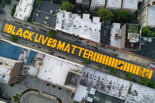 "FILE - In this  June 15, 2020, file photo, a giant ""BLACK LIVES MATTER"" sign is painted in orange on Fulton Street, Monday, June 15, 2020, in the Brooklyn borough of New York. Black Lives Matter Global Network Foundation, the group behind the emergence of the Black Lives Matter movement, has established a more than $12 million fund to aid organizations fighting institutional racism in the wake of the George Floyd protests."