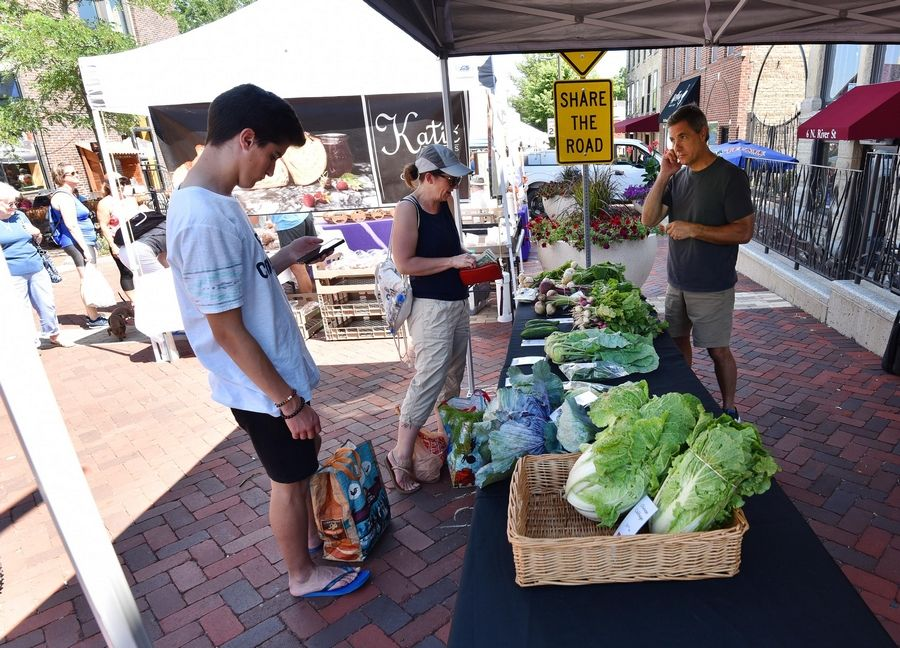 Mike Petersdorf of Muirhead Farms of Hampshire talks with customers at the Batavia Farmers Market. The market is open on Saturdays with social distancing guidelines. It is also offering preordering and delivery of items.