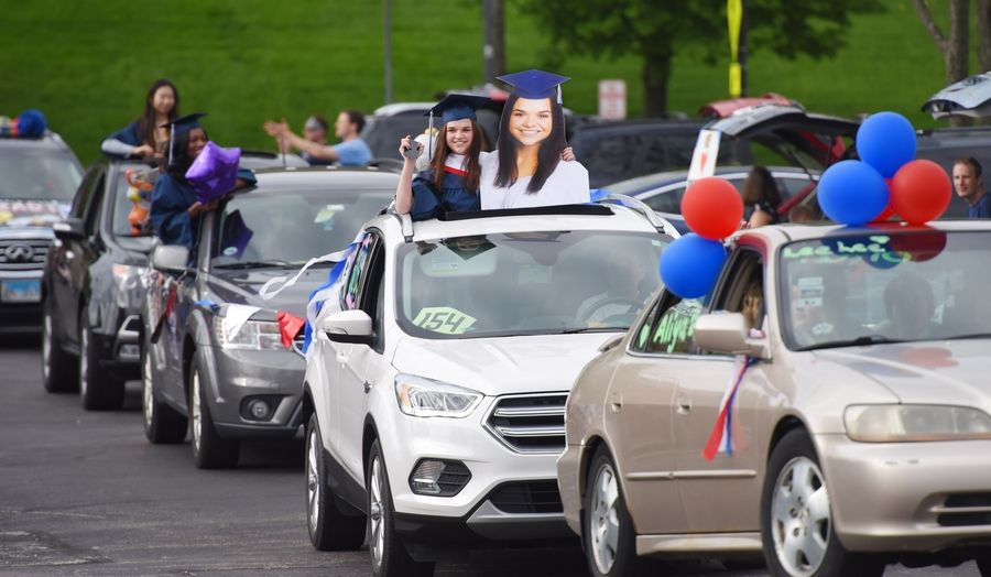 Conant High School graduate Kelly Gregory holds a likeness of herself during a sendoff parade for seniors at Boomers Stadium in Schaumburg. With almost 600 graduates, the parade lasted three hours.
