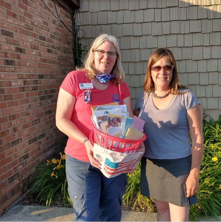 Sonya Stowers, left, of Chicagoland Blue Star Mothers accepts a basket of letters for the military from Sarah Starke, executive director of DoodleBug Workshop in Wheaton.