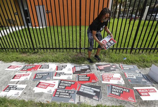 Kelli Ann Thomas, a candidate for Community Council, sorts signs before the start of a Workers First Caravan, Wednesday, June 17, 2020, in Miami. The caravan was part of a nation-wide effort to urge those in government to implement policies that further economic and racial justice.