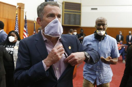 Virginia Gov. Ralph Northam, left, dons a mask as he leaves a news conference after announcing his plans to remove the statue of Confederate General Robert E. Lee on Monument Avenue Thursday June 4, 2020, in Richmond, Va.