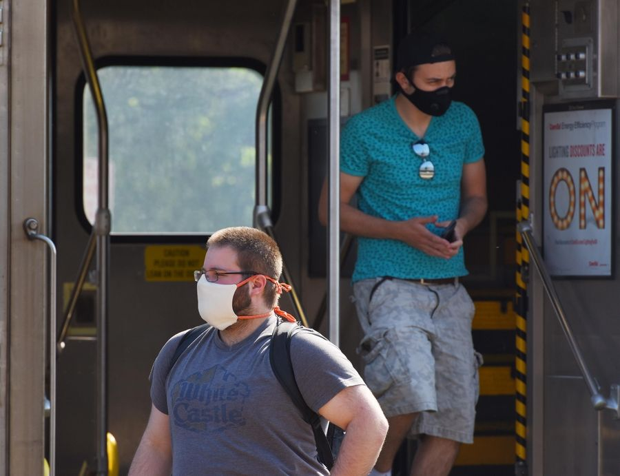 John Starks/jstarks@dailyherald.comMetra passengers exit a train at the Arlington Heights platform Thursday wearing masks to prevent spread of COVID-19.