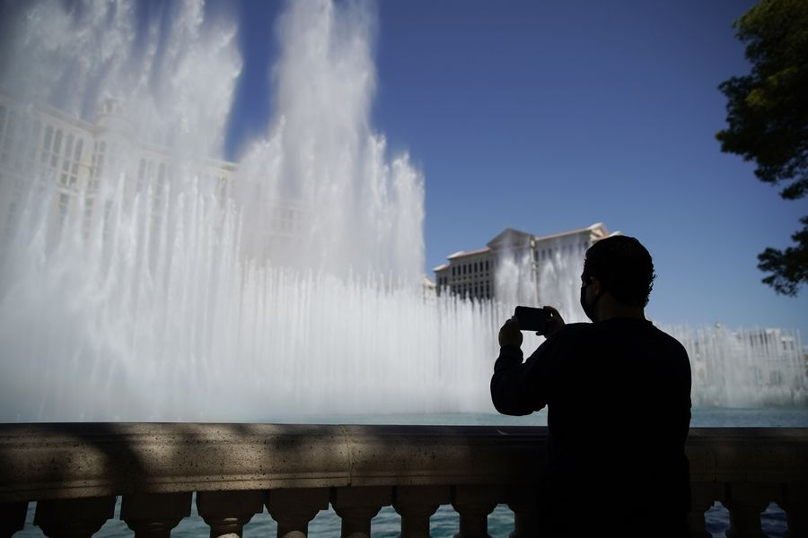 A man watches the fountains before the reopening of the Bellagio hotel and casino Thursday, June 4, 2020, in Las Vegas. A sharp decline in travel during the COVID-19 pandemic will cost governments roughly $17 billion in revenue from taxes on hotel occupancy, corporate profits and other levies in 2020, according to a study by Oxford Economics.