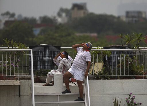 A couple watches solar eclipse from the roof of their house in New Delhi, India, Sunday, June 21, 2020.