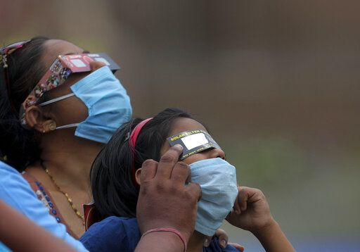 Indians wearing masks as a precaution against coronavirus watch solar eclipse through solar filters in Hyderabad, India, Sunday, June 21, 2020.