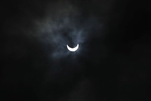 The sun is seen through rain clouds during solar eclipse in Ahmedabad, India, Sunday, June 21, 2020.