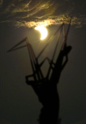 A partial solar eclipse is seen over the Children's Peace Monument at Hiroshima Peace Memorial Park in Hiroshima, western Japan Sunday, June 21, 2020. (Kyodo News via AP)