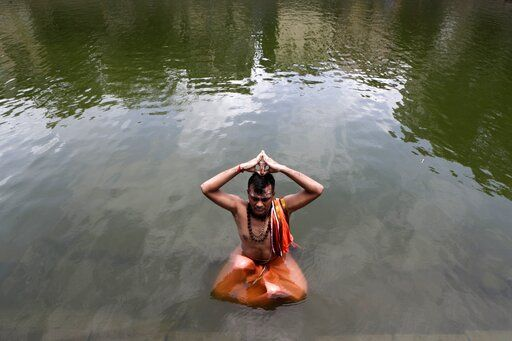 A Hindu devotee sits in a pond and performs rituals during solar eclipse at Banganga in Mumbai, India, Sunday, June 21, 2020.