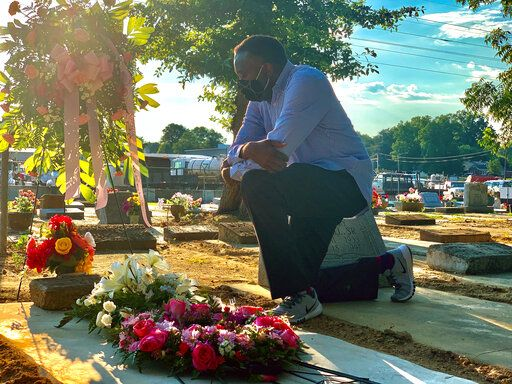 Will Boyd kneels at the grave of a family member who died after contracting the coronavirus, Saturday, June 20, 2020, in Montgomery, Ala. He says his family has lost multiple family members to COVID-19.