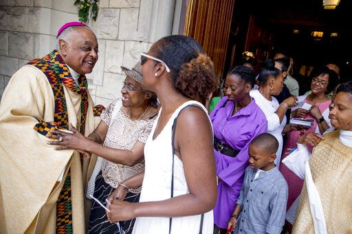 FILE - In this Sunday, June 2, 2019 file photo, Archbishop of Washington Wilton Gregory, left, greets parishioners following Mass at St. Augustine Church in Washington. In June 2020, Gregory, the first African-American in charge of the Archdiocese of Washington, joined with eight fellow bishops from his region to acknowledge the church's 'œsins and failings'� in regard to racial justice. 'œPrayer and dialogue, alone, are not enough. We must act to bring about true change,'� the bishops said, calling for more racial equality in health care, education, housing and criminal justice.