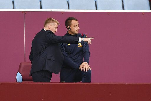 Aston Villa's head coach Dean Smith, left and assistant coach John Terry on stands during the English Premier League soccer match between Aston Villa and Chelsea at the Villa Park stadium in Birmingham, England, Sunday, June 21, 2020. (Justin Tallis/Pool via AP)
