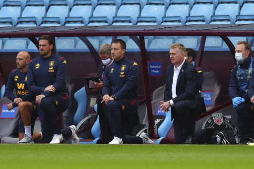 Aston Villa's head coach Dean Smith, center right and assistant coach John Terry kneel ahead of the English Premier League soccer match between Aston Villa and Chelsea at the Villa Park stadium in Birmingham, England, Sunday, June 21, 2020. (Cath Ivill/Pool via AP)