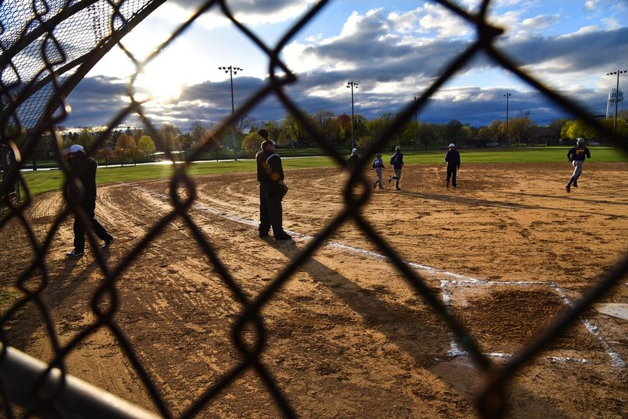 Umpire David Baker watches as players take the field at a youth baseball game at Kimball Hill Elementary School in Rolling Meadows. Youth sports can resume under Phase 4 of Illinois' reopening plan but with restrictions.