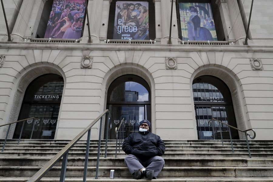 A man sits in front of the Art Institute of Chicago museum in downtown Chicago. Museums can reopen under Phase 4 of Illinois' reopening plan but with restrictions and at 25% capacity.