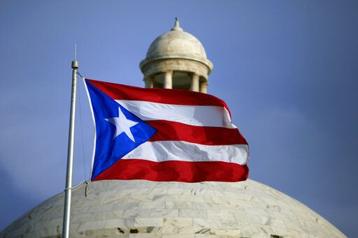 FILE - In this July 29, 2015 file photo, the Puerto Rican flag flies in front of Puerto Rico's Capitol as in San Juan, Puerto Rico. A federal control board that oversees Puerto Rico's finances submitted a proposed $10 billion budget on Thursday, June 11, 2020, as federal legislators debate whether to curtail the board's power over the U.S. territory.