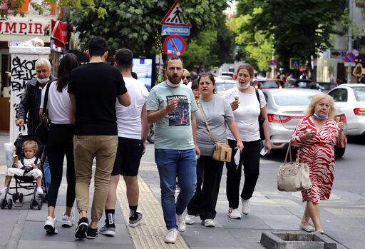 People who are not wearing face masks to protect against the spread of coronavirus, walk in city the centre, in Ankara, Turkey, Sunday, June 21, 2020. Turkish authorities have made the wearing of masks mandatory in three major cities to curb the spread of COVID-19 following an uptick in confirmed cases since the reopening of many businesses.