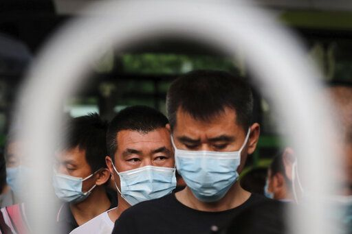 Commuters wearing protective face masks to help curb the spread of the new coronavirus line up to board a bus at a bus terminal in Beijing, Monday, June 22, 2020. A Beijing government spokesperson said the city has contained the momentum of a recent coronavirus outbreak that has infected a few hundreds of people, after the number of daily new cases fell to single digits.