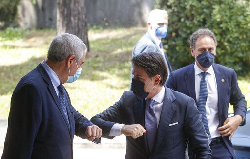 Italian Premier Giuseppe Conte, right, touch elbows with Civil Protection head Angelo Borrelli as he arrives for a thanksgiving ceremony dedicated to physicians and nurses, in Rome, Monday, June 22, 2020.