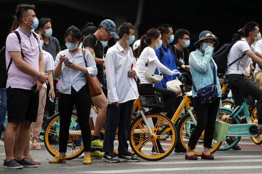 People wearing protective face masks to help curb the spread of the new coronavirus wait to cross a street in Beijing, Monday, June 22, 2020. A Beijing government spokesperson said the city has contained the momentum of a recent coronavirus outbreak that has infected a few hundreds of people, after the number of daily new cases fell to single digits.
