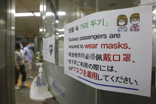 "A notice on precautions against the new coronavirus is displayed at a subway station in South Korea, Monday, June 22, 2020. The sign at top reads: ""Social distance."""