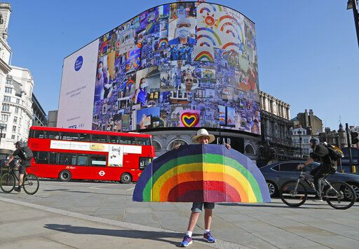 A young boy holds a painted rainbow as pictures appear on a screen during a 10 minute domination on The Piccadilly Lights, Piccadilly Circus, to mark the launch of The People's Picture interactive mosaic art project Rainbows for the NHS in London, Monday, June 22, 2020. The art installation which features thousands of photos and messages from key workers, carers, patients, doctors and nurses appears on Piccadilly Lights until June 28.