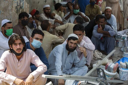 Unmasked daily wage workers wait to be hired by customers in Rawalpindi, Pakistan, June 12, 2020. Pakistan ranks among countries hardest hit by the coronavirus with infections soaring beyond 18,000, while the government, which has opened up the country hoping to salvage a near collapsed economy, warns a stunning 1.2 million Pakistanis could be infected by the end of August.