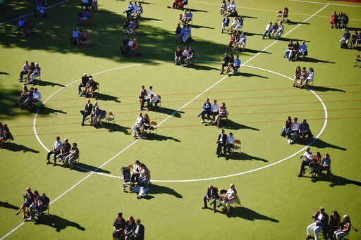 High school graduates and their relatives sit in distance on the sports field during the graduation ceremony at the Rheingau Gymnasium in Berlin, Germany, Tuesday, June 23, 2020. The coronavirus distance rules to avoid the spread are observed during the ceremony. (Kay Nietfeld/dpa via AP)