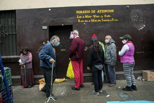 People wait in a line to receive free food at La Parada market in La Victoria district of Lima, Peru, Tuesday, June 23, 2020. Many businesses reopened Monday in Peru after a mandatory closure that began on March 16 with the start of a quarantine aimed at slowing the advance of the new coronavirus.