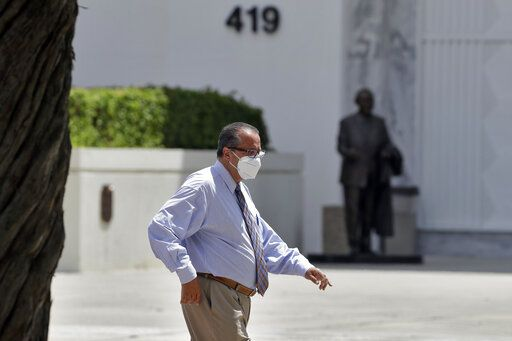 A man wearing a protective mask walks past a county office building Tuesday, June 23, 2020, in Tampa, Fla. Members of the Hillsborough County Emergency Policy Group voted 5-3 on Monday to implement an executive order that would require the wearing of protective face coverings throughout Hillsborough County. The executive order requires everyone inside a for-profit business that is open to the public to wear a mask when social distancing cannot be maintained, excluding family members or others residing in your home.