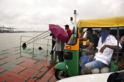 Commuters wearing masks as a precaution against the coronavirus travel in a ferry during rain in Kochi, Kerala state, India, Monday, June 22 2020. India is the fourth hardest-hit country by the COVID-19 pandemic in the world after the U.S., Russia and Brazil.
