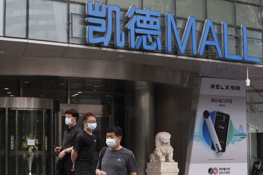 People wearing protective face masks to help curb the spread of the new coronavirus gather outside a shuttered shopping mall following positive cases detected at the mall in Beijing, Tuesday, June 23, 2020. China reported close to two dozen new cases of coronavirus on Tuesday a day after a city government spokesperson said containment measures had slowed the momentum of an outbreak in the capital that has infected more than 200 people.