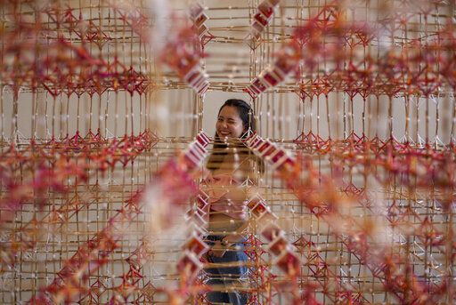 A woman looks through an art installation of Rattana Sudjarit at the Bangkok Art and Cultural Center in Bangkok, Thailand, Tuesday, June 23, 2020. Daily life in the capital is resuming to normal as the Thai government continues to ease restrictions related to running business and activities that were imposed weeks ago to combat the spread of COVID-19.
