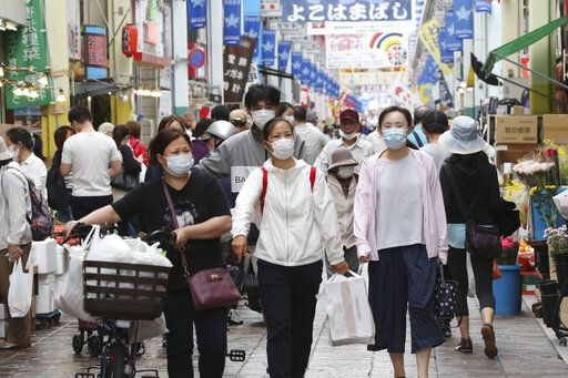 People wearing face masks shop at a mall in Yokohama, near Tokyo, Tuesday, June 23, 2020. Japan's economy is opening cautiously, with social-distancing restrictions amid the coronavirus pandemic.