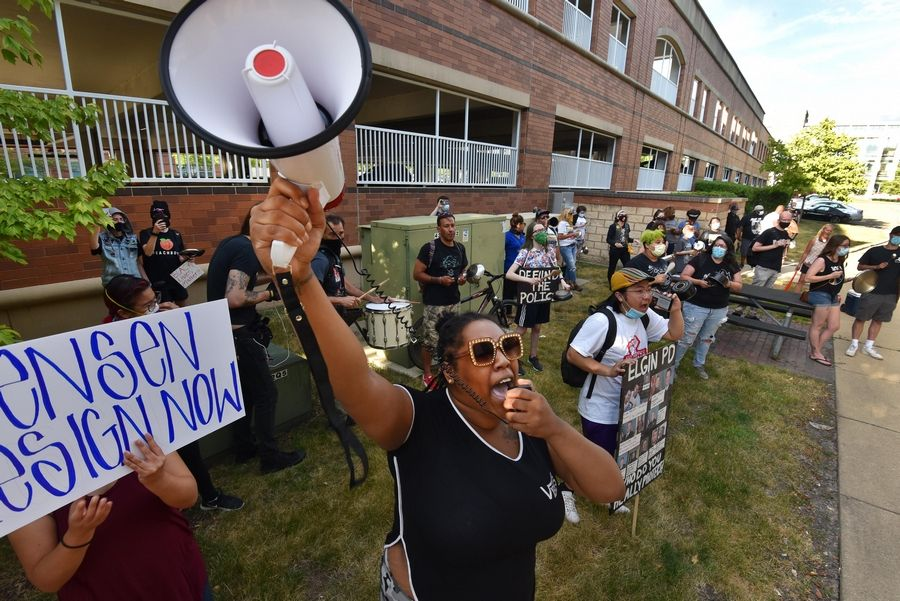 Shakenna Banks uses a megaphone at the Elgin in Solidarity with Black Lives Matter protest as others use pots and pans to make noise outside city hall before the council meeting Wednesday.