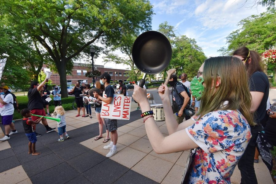 The Elgin in Solidarity with Black Lives Matter protest group uses pots and pans to make noise outside city hall Wednesday.