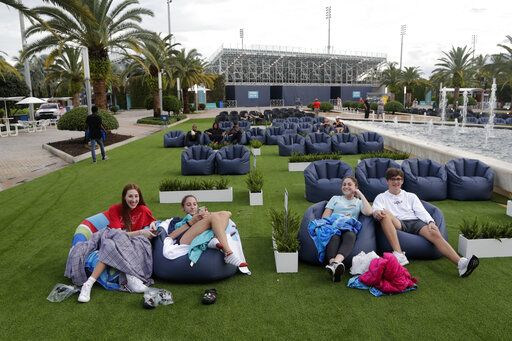 FILE - In this Thursday, June 18, 2020 file photo, people sit outdoors to watch a movie as part of a program offered by the Miami Dolphins at Hard Rock Stadium during the coronavirus pandemic in Miami Gardens, Fla. Elected officials such as Florida's governor have argued against reimposing restrictions, saying many of the newly infected are young and otherwise healthy. But younger people, too, face the possibility of severe infection and death. And authorities worry that older, more vulnerable people could be next.