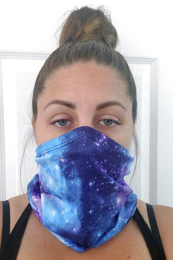 This June 23, 2020 photo provided by Kristen Kowall, 32, of Clearwater, Fla., shows her wearing a mask. In Florida, where many restaurants and bars reopened in early May, Kowall dined out with her fiance in early June. Like others in the restaurant, she didn't wear a mask. Later she tested positive for COVID-19. 'œI just feel really groggy and tired. It hurts to walk. Especially my ankles and knees, it feels like my bones are going to fall apart,'� she said. 'œI definitely would advise people from going out. It's not worth it.'� (Kristen Kowall via AP)