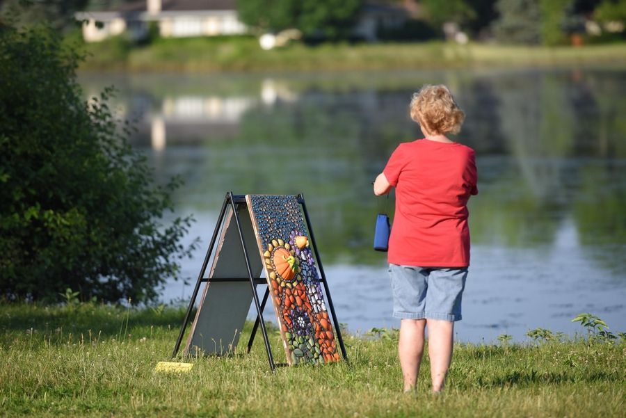 A walker stops to take a photograph of a mosaic by artist June Nichols on the shore of Hillcrest Lake in Prospect Heights.